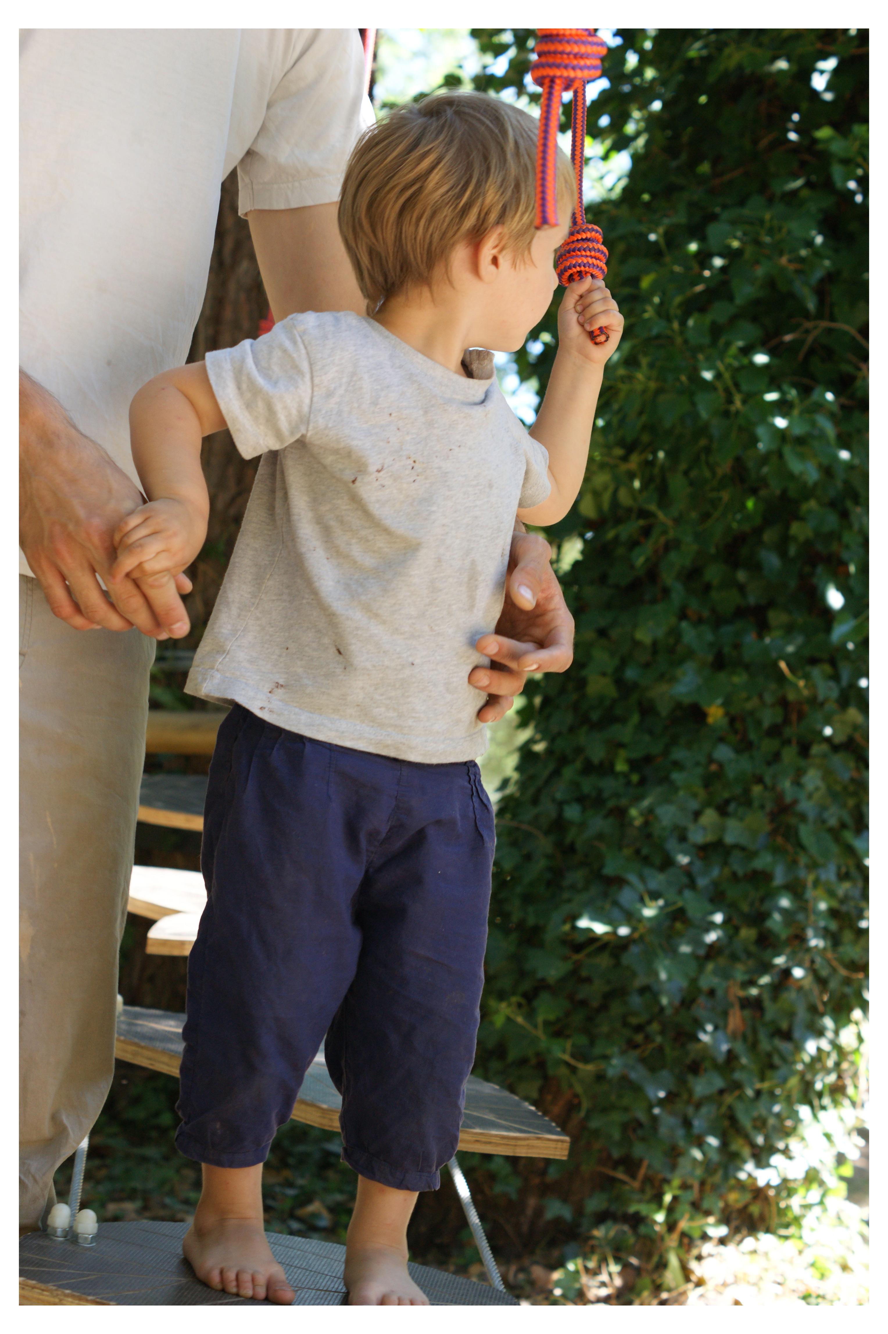 papa offrant un soutien à son fils lors d'un acrobranche