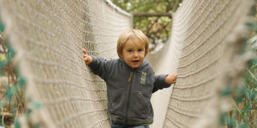 enfant fier de lui dans un pont suspendu