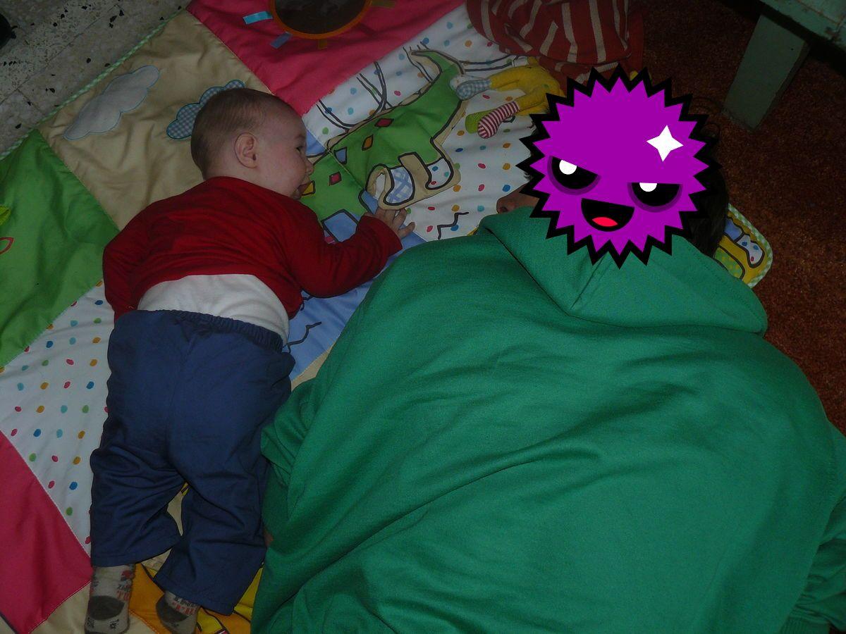 papa à côté de son fils allongé sur un tapi déveil